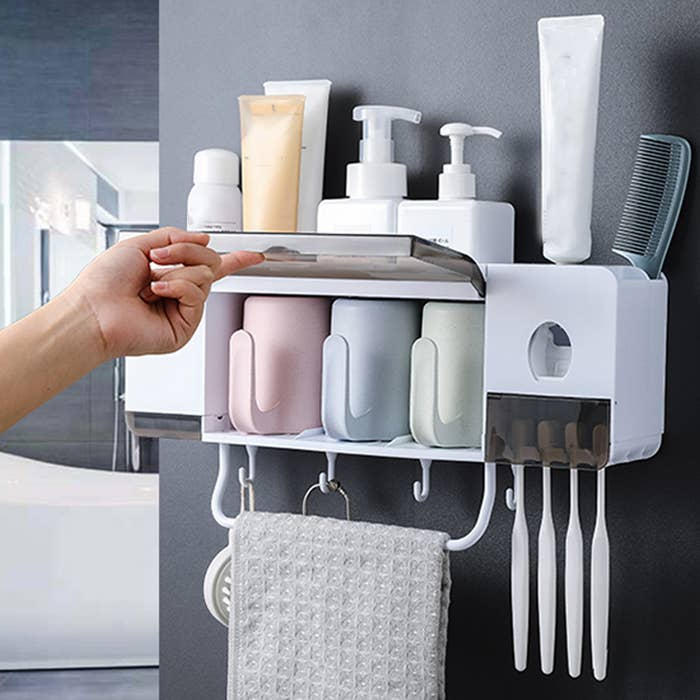 A person opening up the lid on the hanging organize where the cups are stored