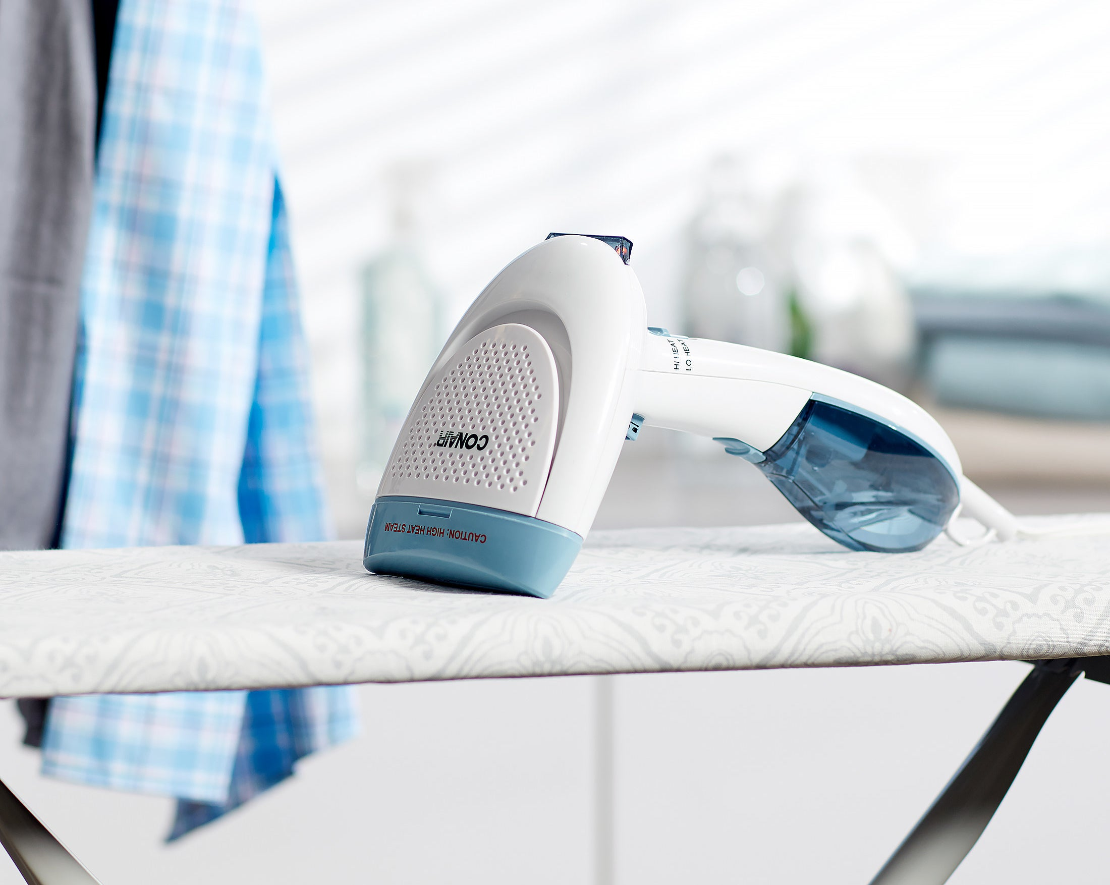 The clothing steamer on top of an ironing board