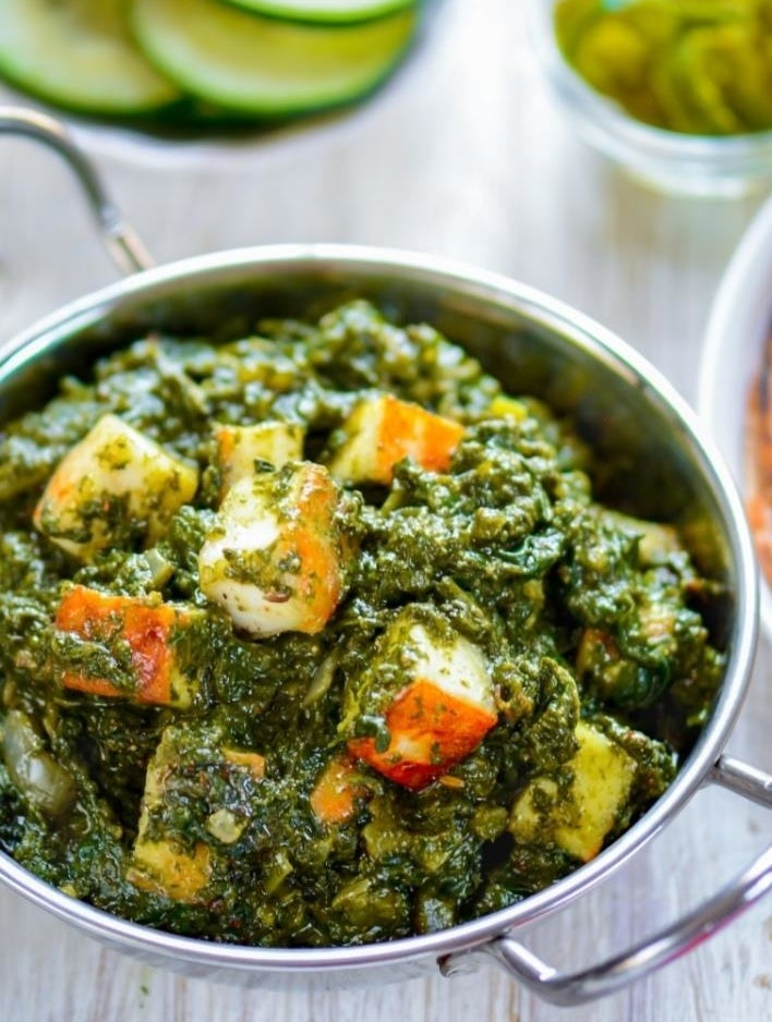A bowl of creamy saag with fried paneer cheese.
