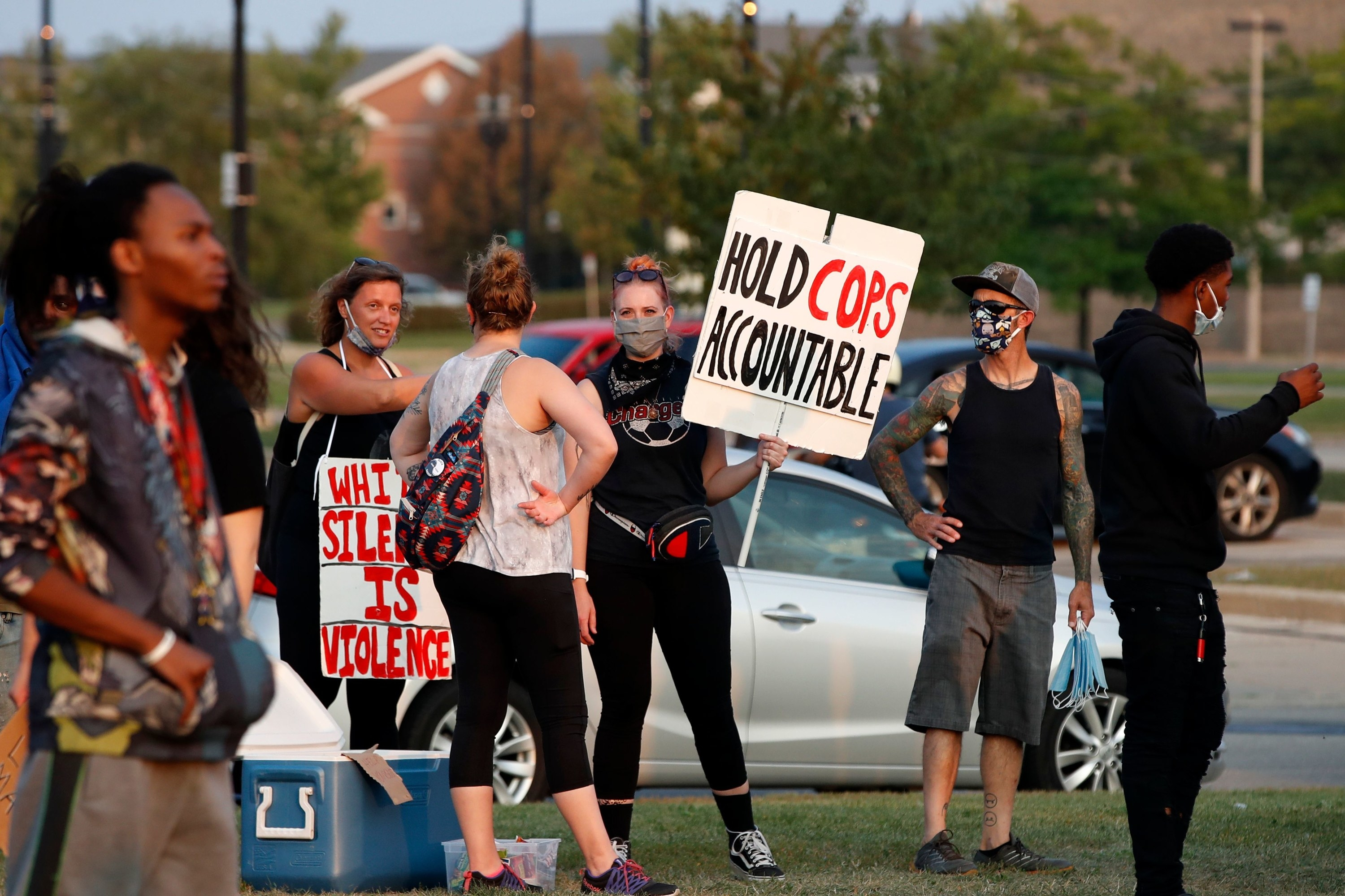 """A white woman in a small group holds a sign saying """"hold cops accountable"""""""