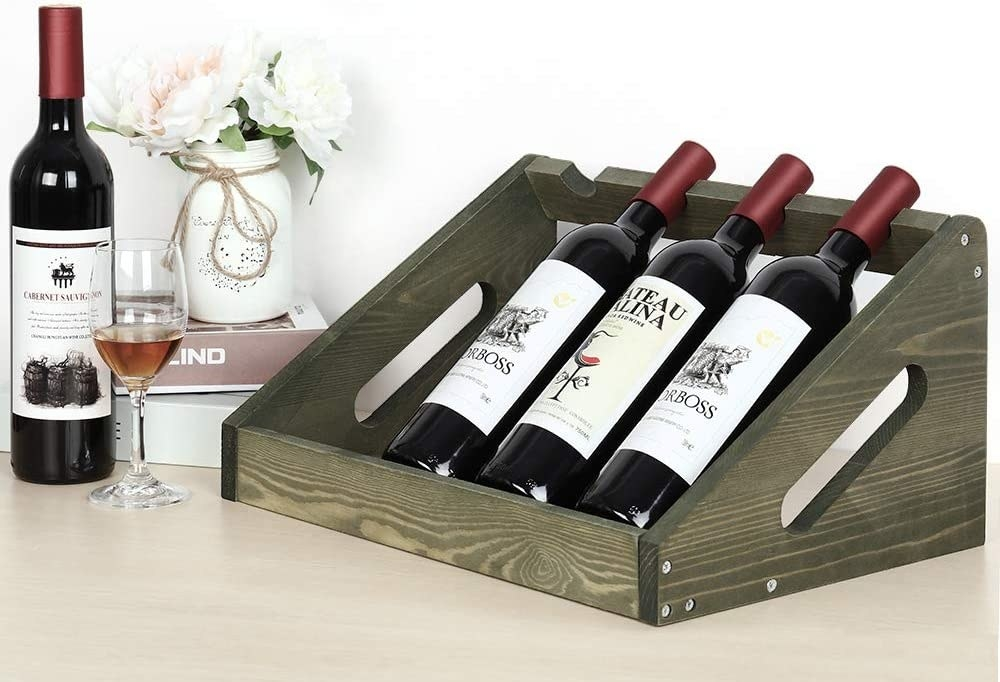 The whine bottle holder holding three bottles of wine with room for one more