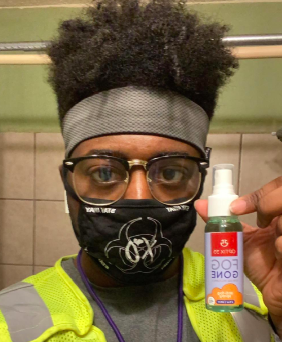 Reviewer photo showing reviewer holding a bottle of anti-fog spray and showing their face with a cloth mask on as well as glasses which appear to not be fogged