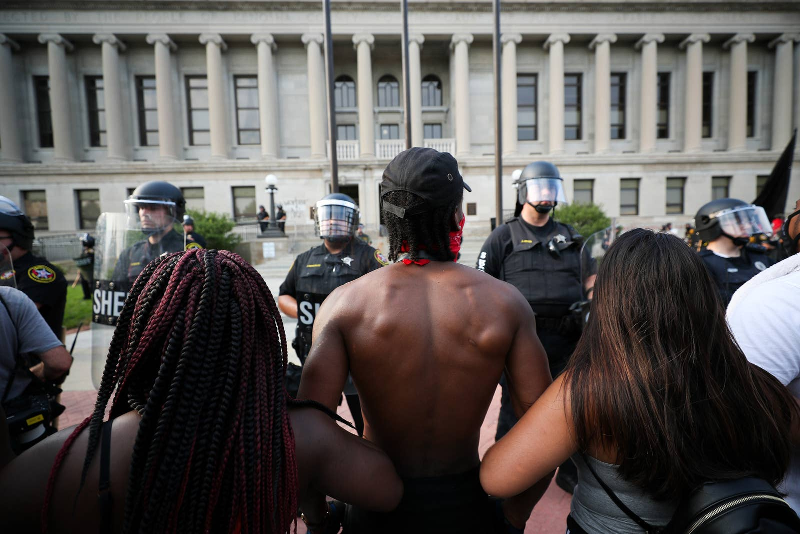 A black man from behind with his arms linked to other protesters faces off with police in riot gear in front of the courthouse