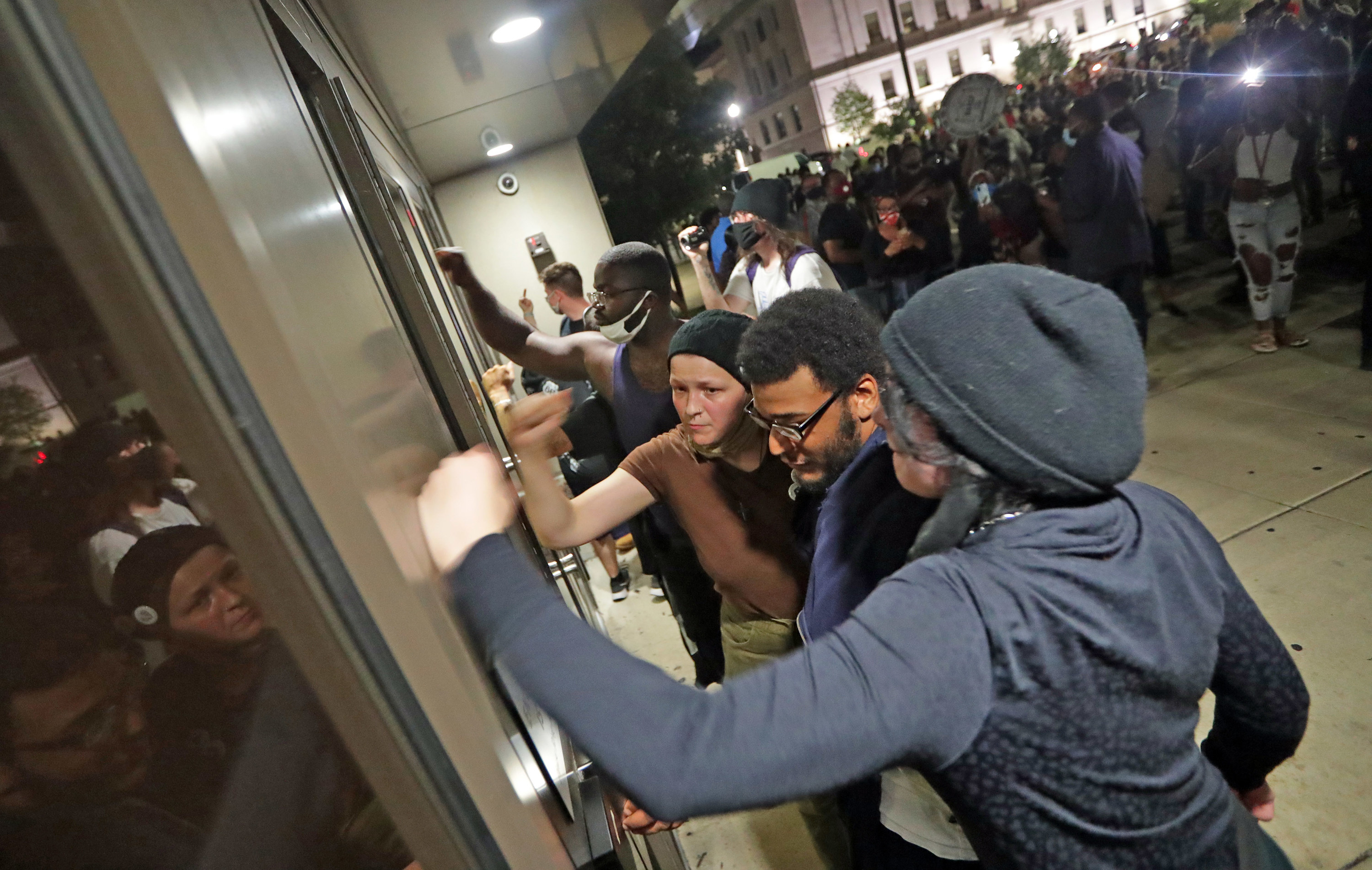 Three people pound on a door with a larger crowd behind them