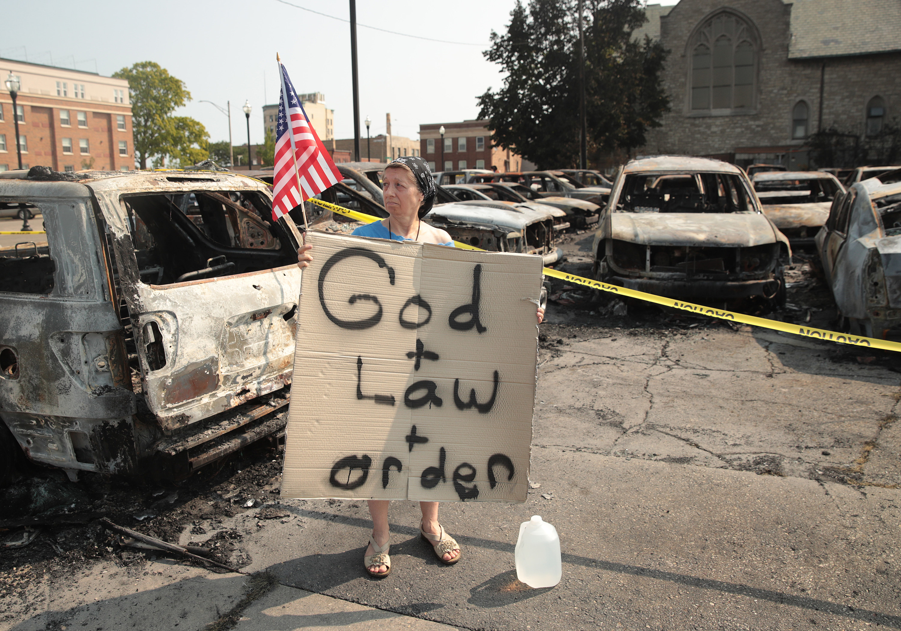 A woman holds a small American flag and a cardboard sign that says god + law + order