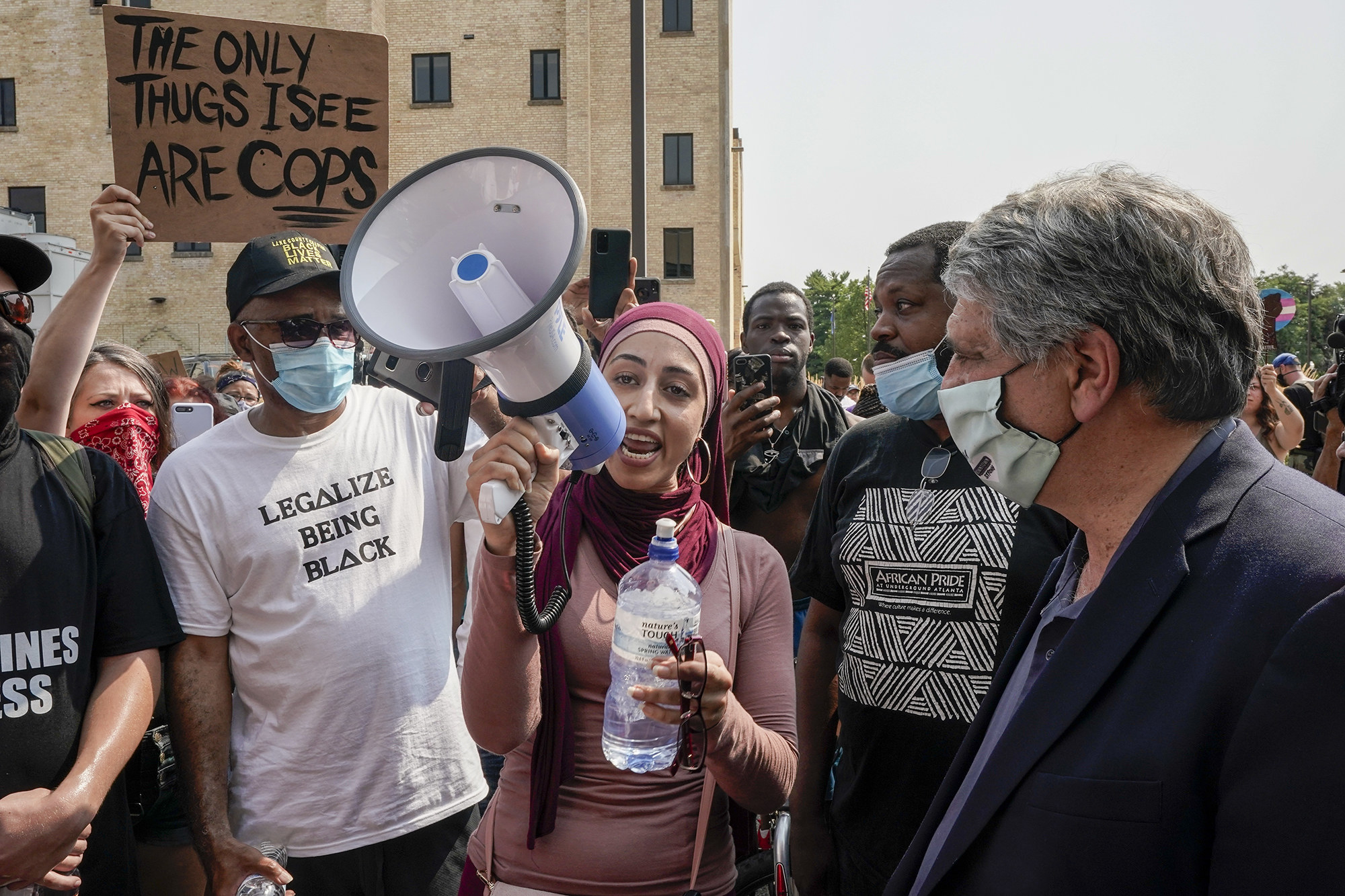 A woman with a pink hijab speaks on a megaphone amidst a crowd