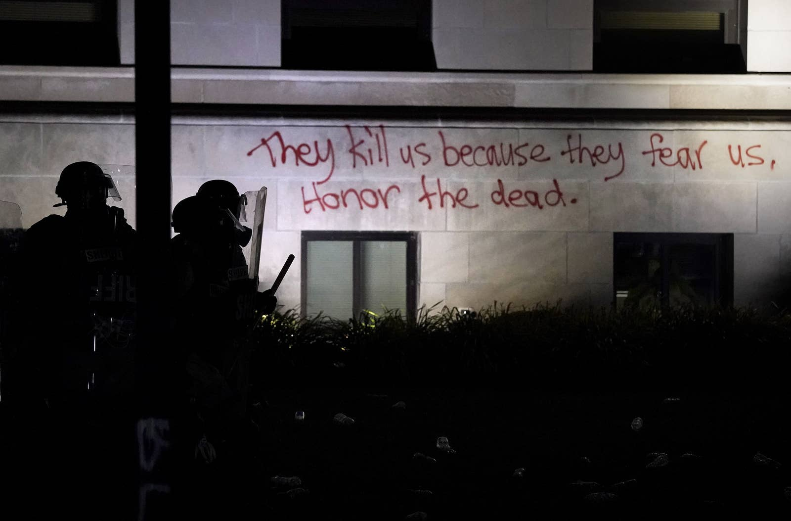 """Spraypaint on the outside wall of the courthouse reads, """"They kill us because they fear us. Honor the dead."""""""