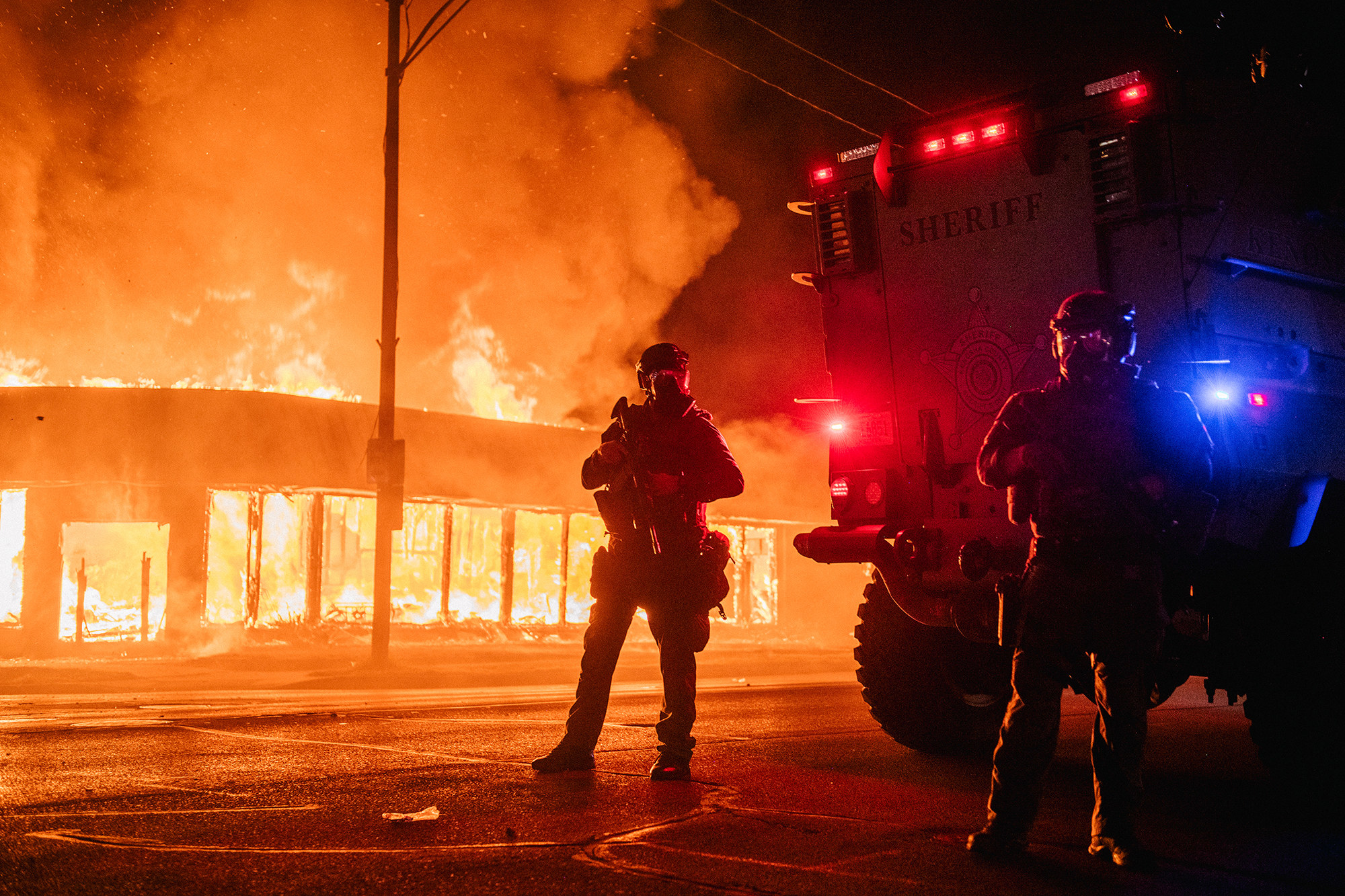 Two police in riot gear stand in front of a burning building