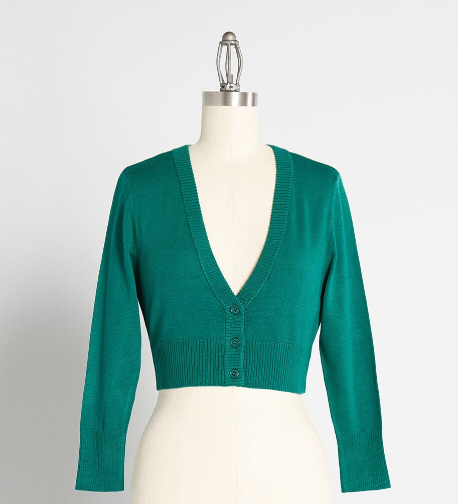The cardigan in green with 3/4 sleeves, ribbed hem and sleeves, and three buttons