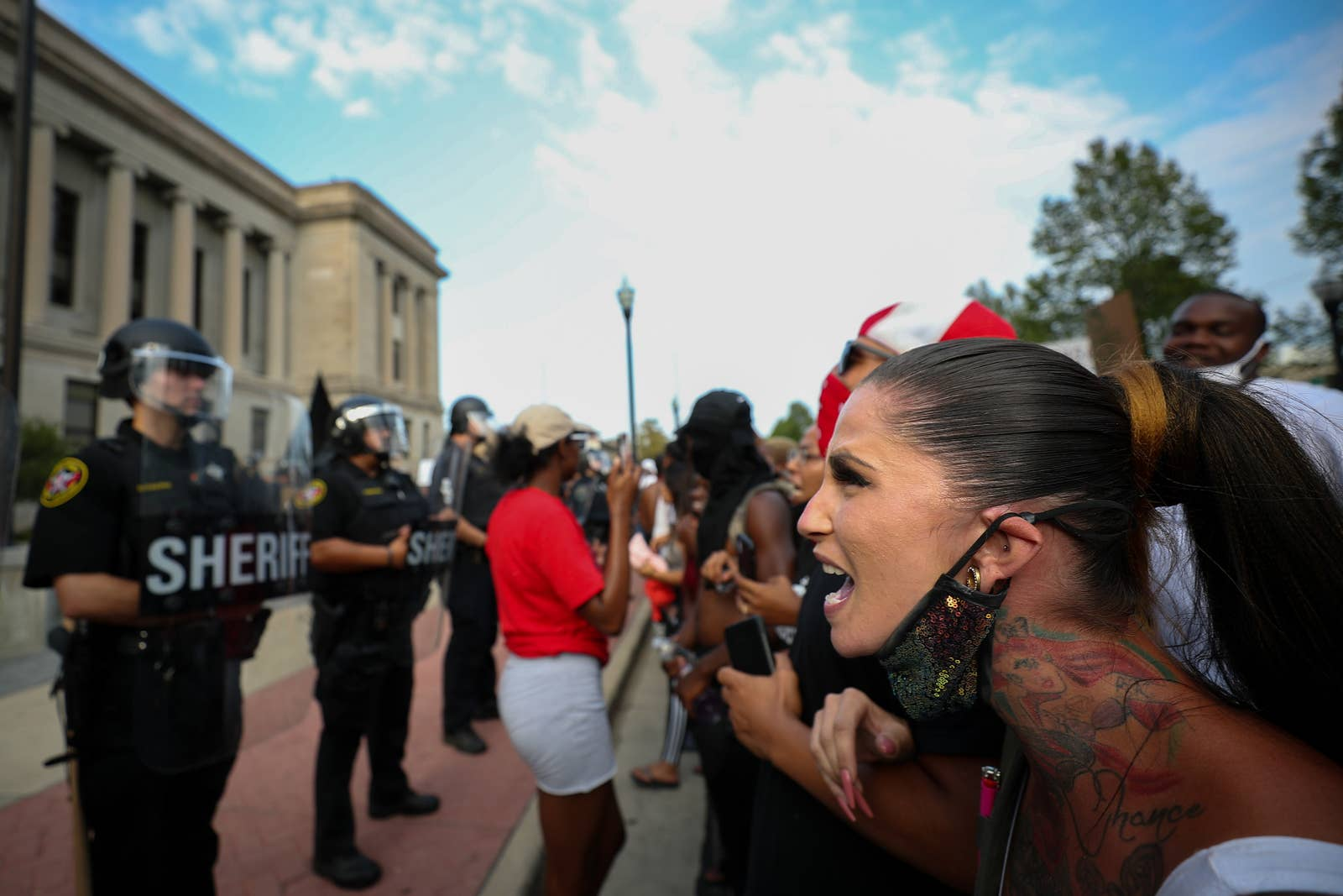 A white woman yells while linking arms with other protesters in front of a line of police in riot gear