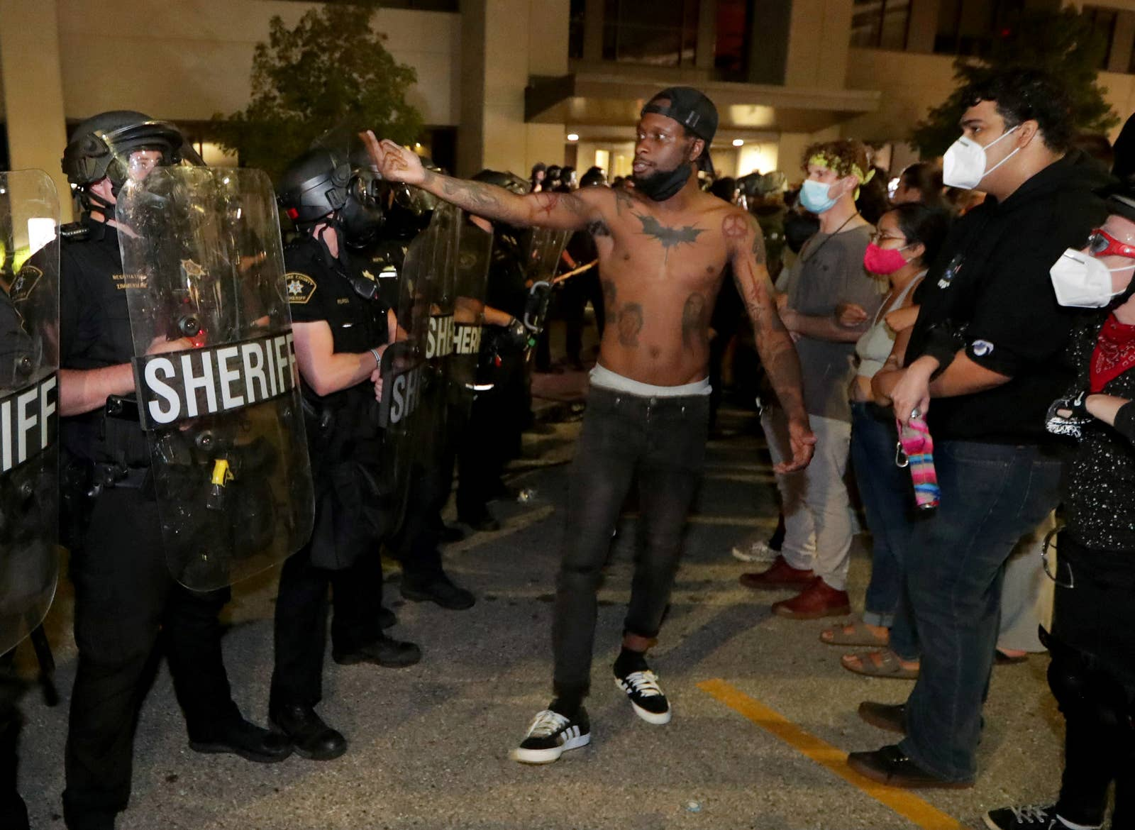 A shirtless Black man uses gestures with his pointer and middle finger raised to a line of police with a crowd next to him