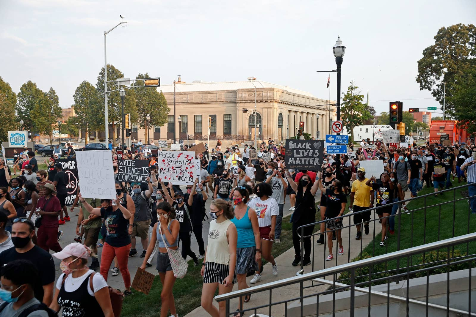 A large crowd of people walk down the street in the afternoon with signs