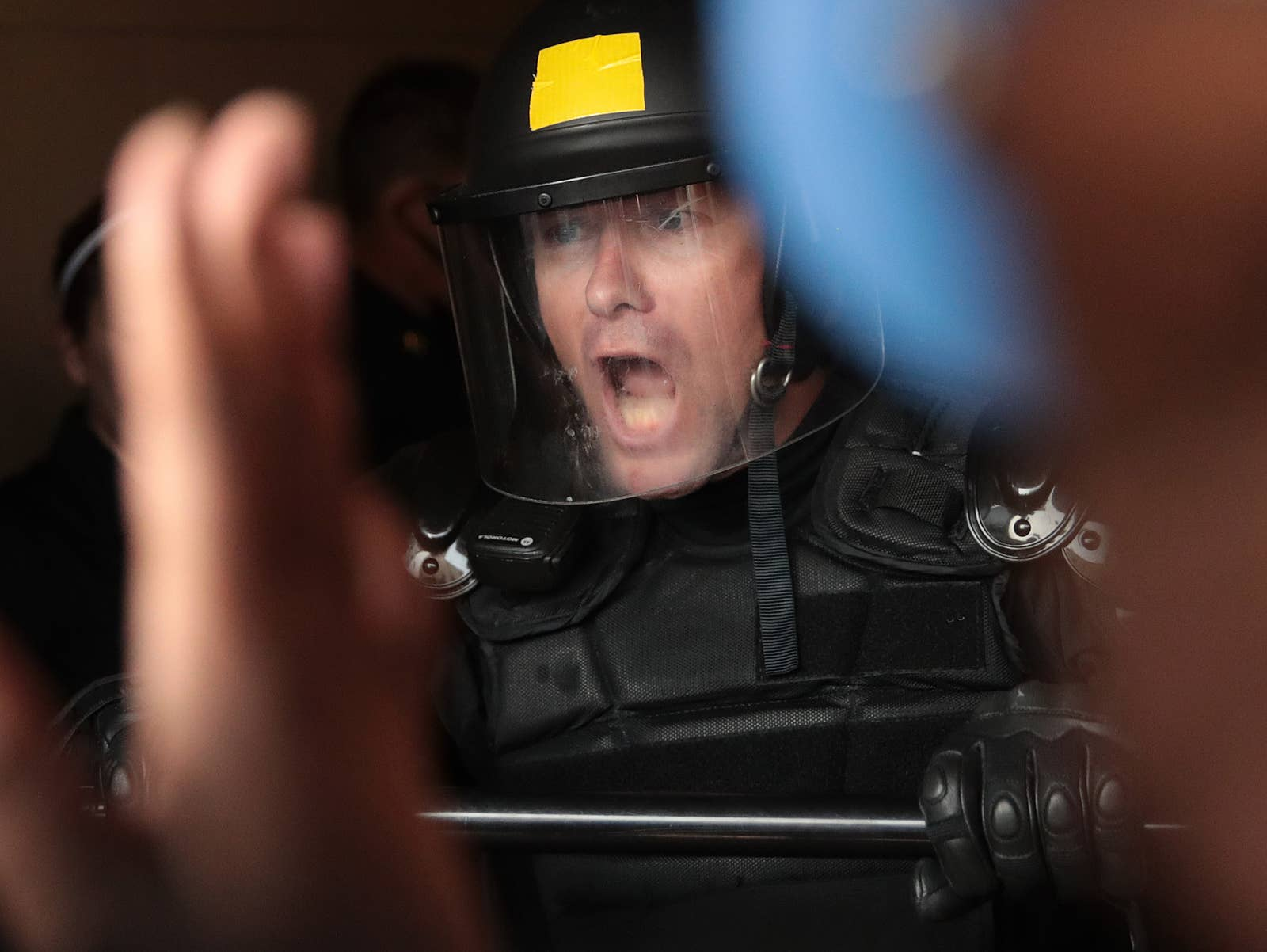 A white police officer in riot gear and a face shield yells