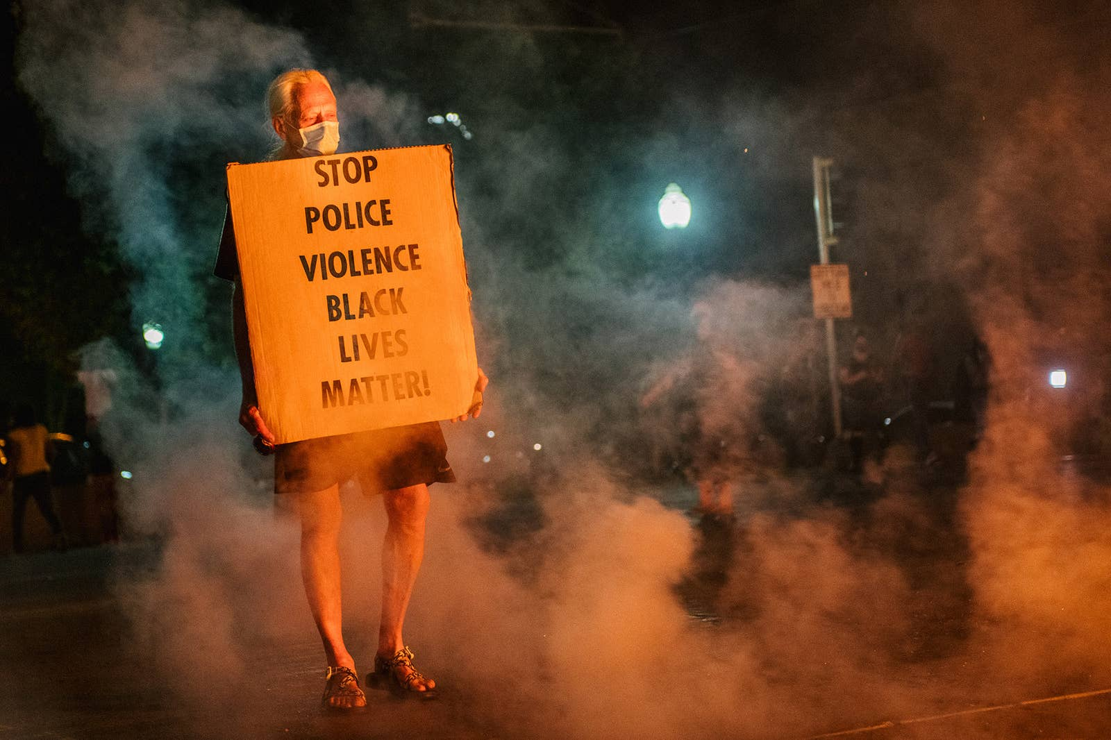 """A man stands with a sign reading """"stop police violence, black lives matter"""""""