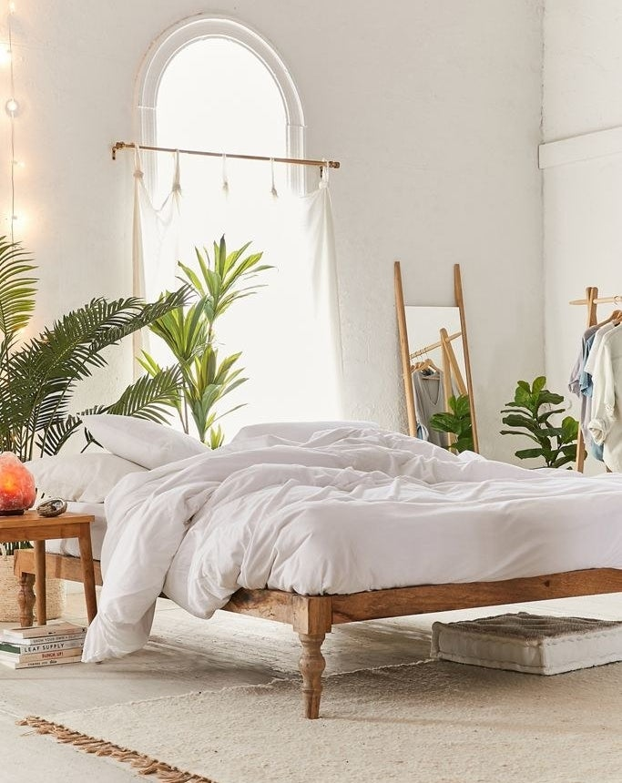 A wooden bed platform with no headboard holding a bed with only a white comforter and white pillows. The bed sits near an arched window, while the rest of the room has a small wooden table, a rug, a wooden mirror, and plant situated around the bed.