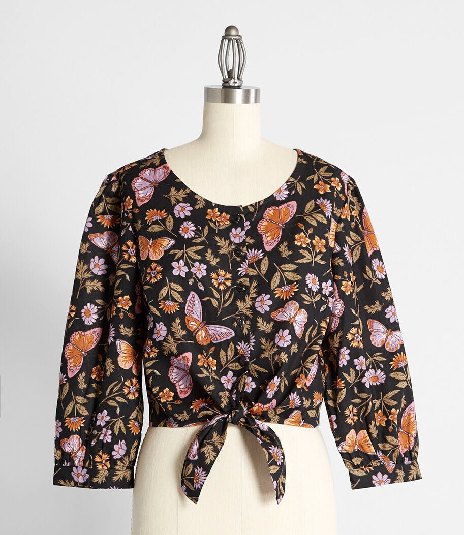 The black scoop-neck blouse with 3/4 sleeves, buttons down the middle, and lilac, orange, and brown butterfly and floral print all over it
