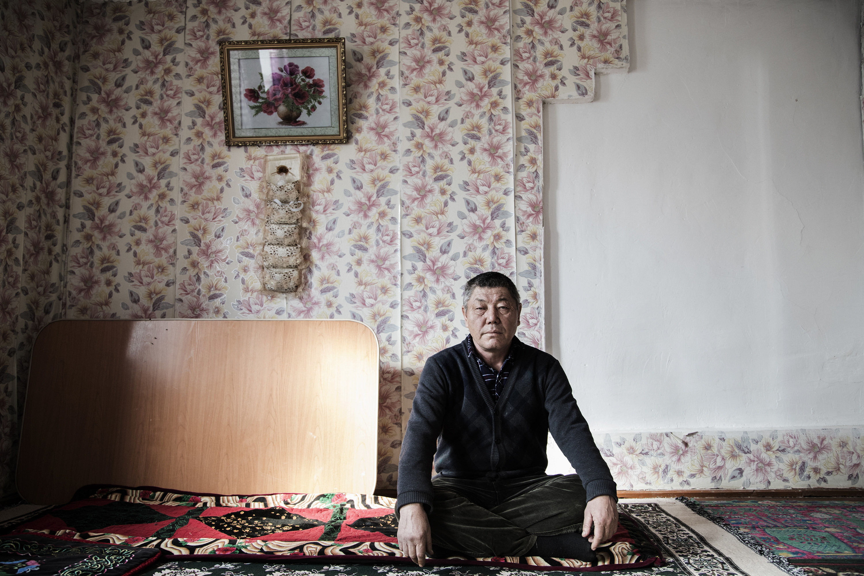 A Uighur man sitting on the floor with his hands on his knees