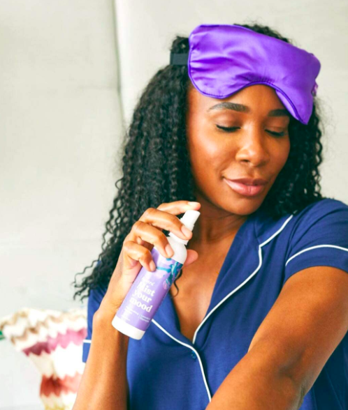 Tennis athlete Venus Williams wearing dark blue pajamas and purple eye mask holding a clear bottle of Astura Lavender & Chamomile Essential Oil Aromatherapy Spray in hand