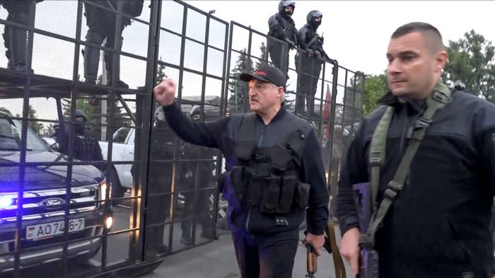 President Alexander Lukashenko carries a rifle while greeting riot police behind a fence