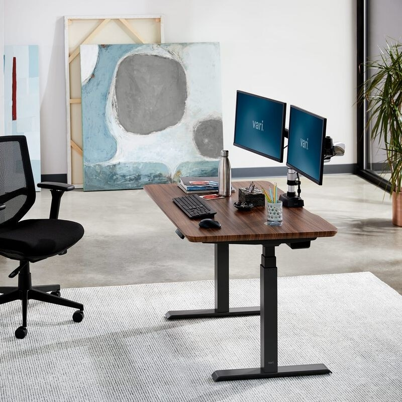 a walnut table top desk with legs that adjust electronically