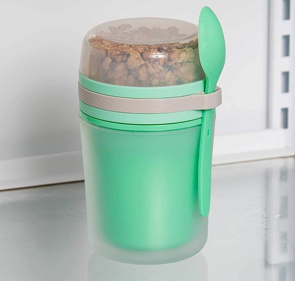 the green container with an attached green spoon and clear top compartment