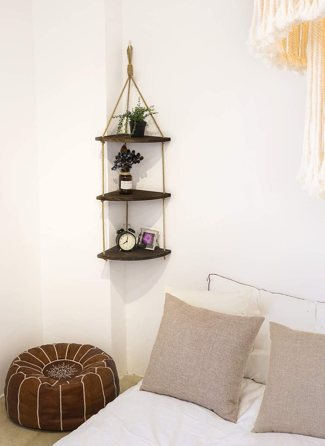 Three tiny triangular shelves hung up with rope in a boho style
