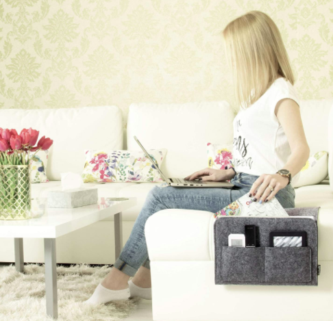 Model sits on a white couch with a laptop while reaching into a dark gray bedside caddy filled with a book, remote, tablet, and smartphone
