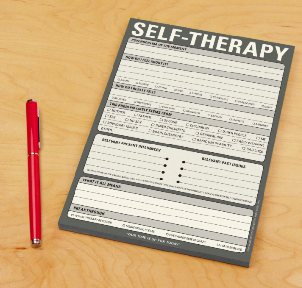 """A gray and white notepad that says """"Self-Therapy"""" at the top next to a red pen"""