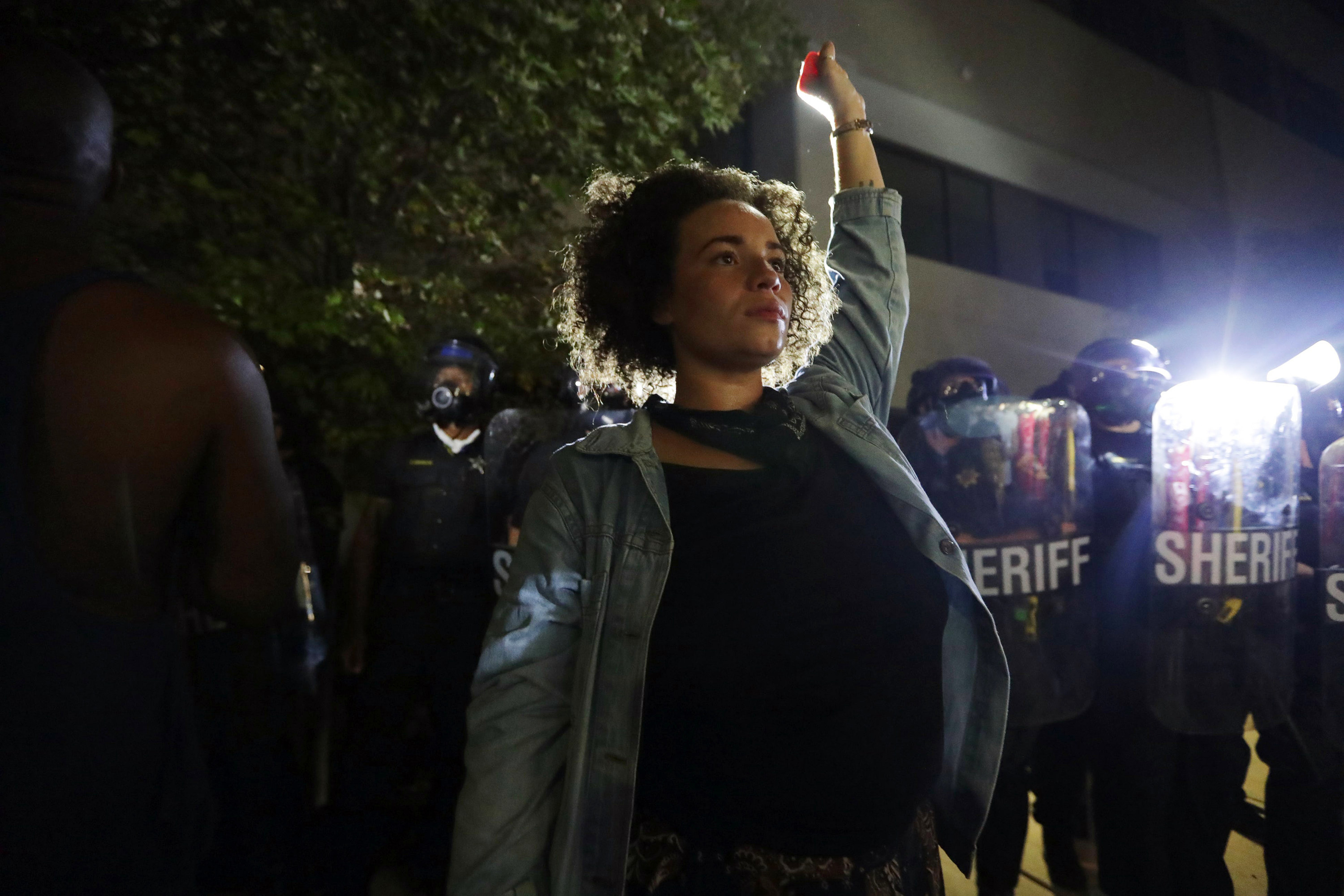 A woman holds her fist up in the air in front of a crowd of police