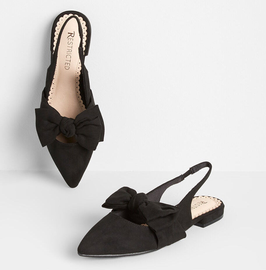 The flats in black suede with pointed toe, elastic sling-back, and a bow across the top