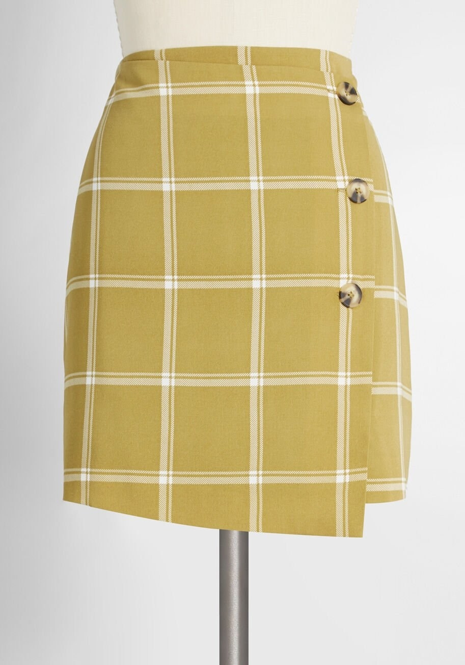 Mini skirt with a side-button closure, asymmetrical front, and a green and white plaid pattern