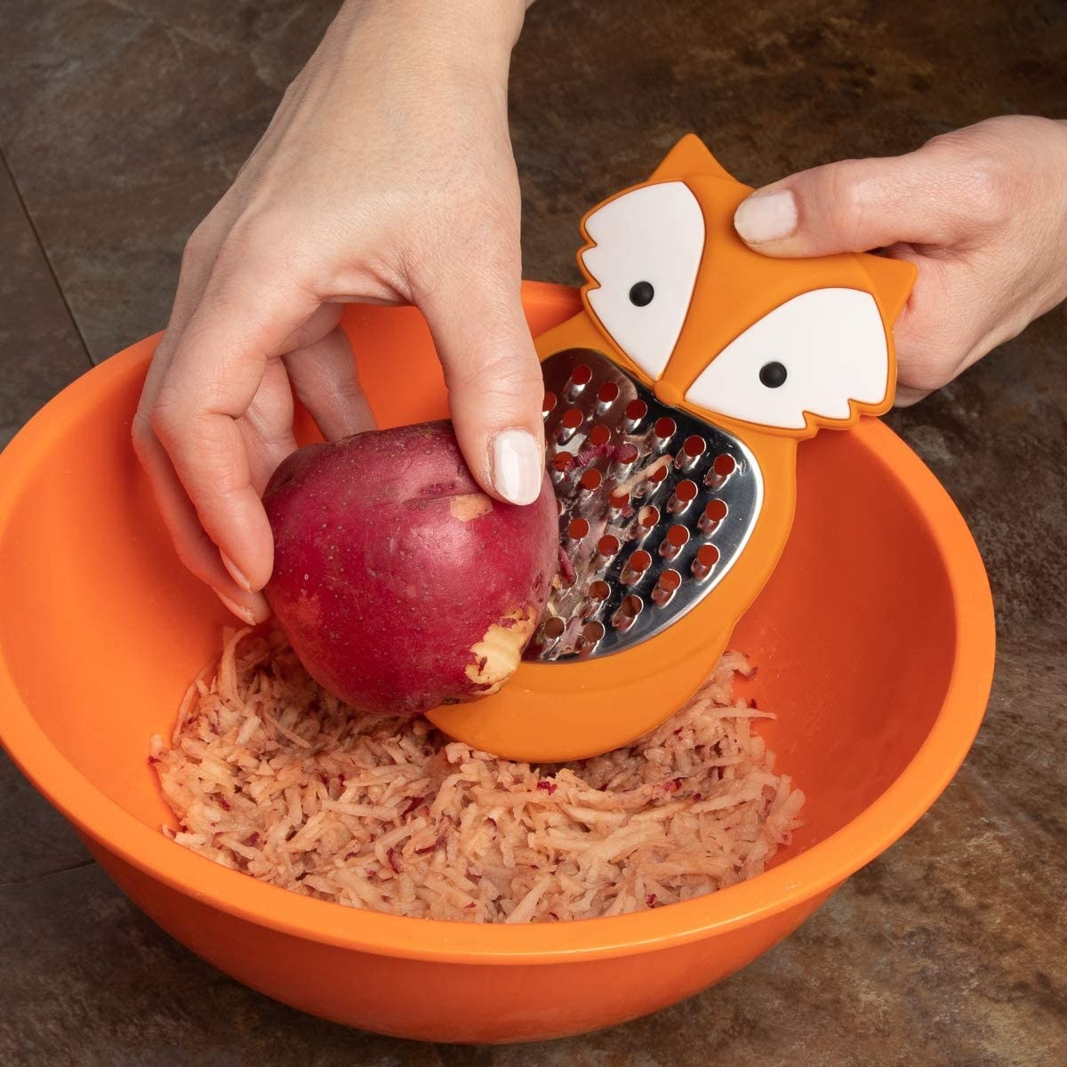 A person grating an apple into a bowl with a small grater with a fox face on the handle