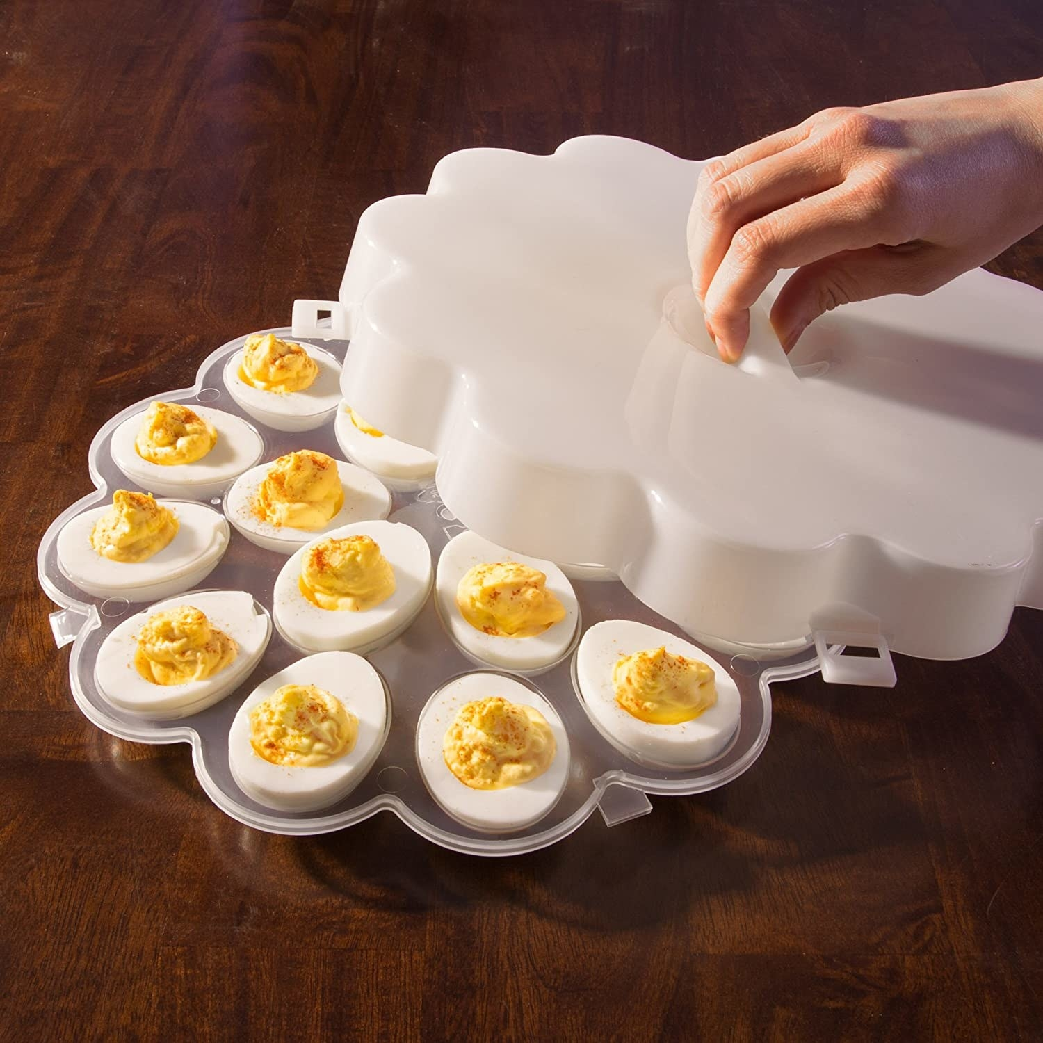A person lifts the lid of the egg tray to show off a dozen perfectly crafted devilled eggs