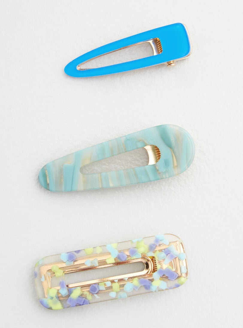 One bright blue clip, a light blue marble-like clip, and a clear rectangular clip with purple, blue, and lime green specks in it