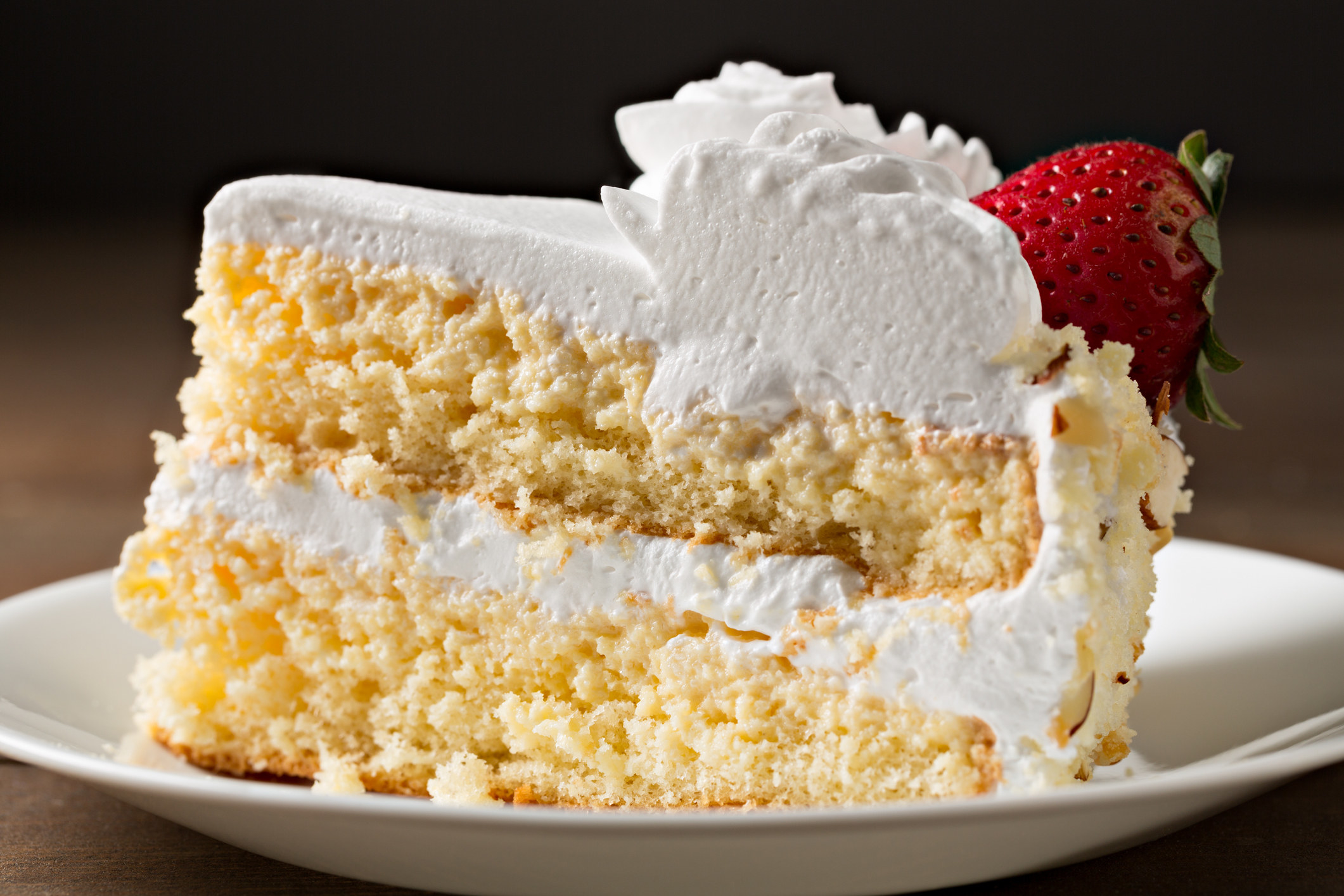 A slice of tres leches cake with a strawberry on it.