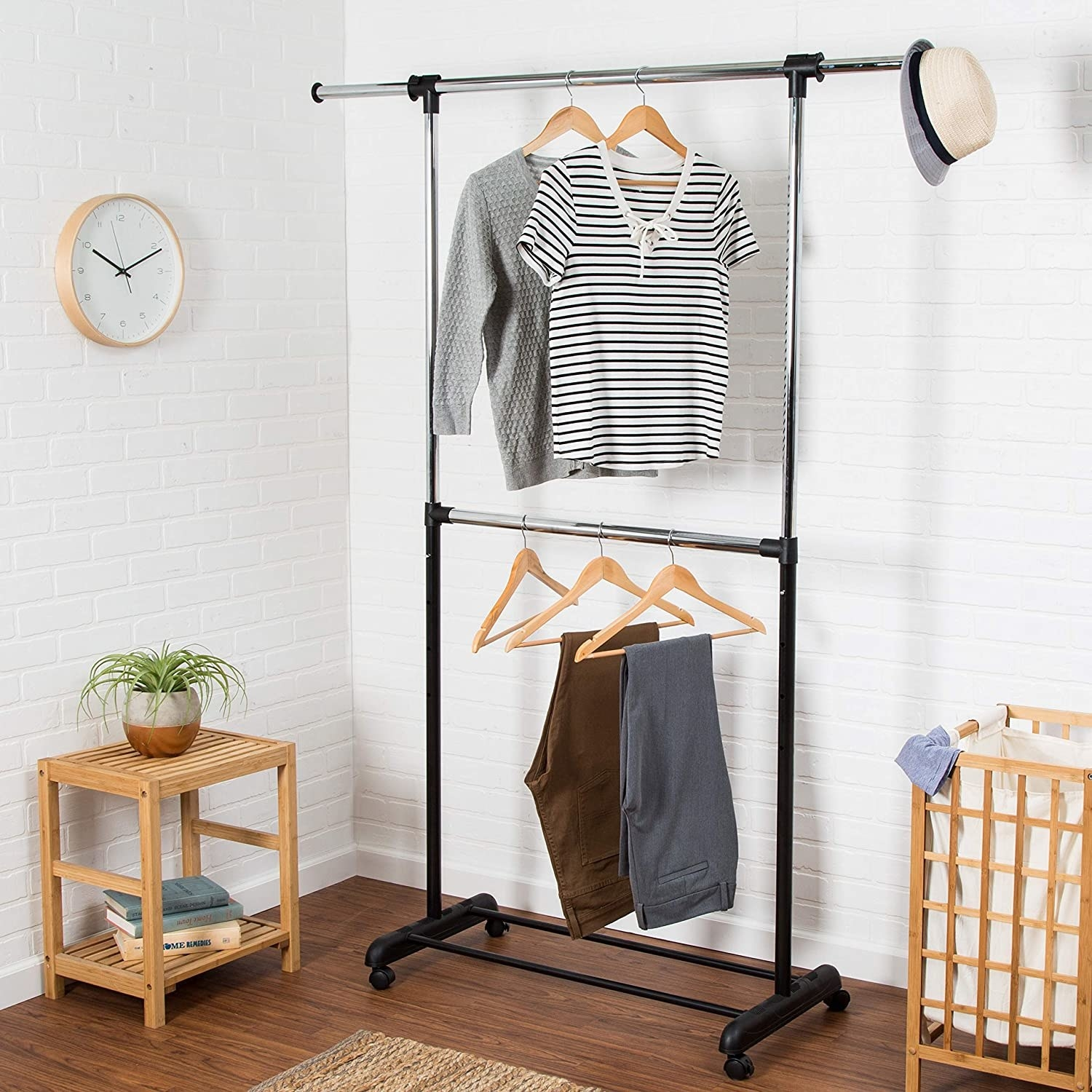 The garment rack containing two shirts and two pairs of pants in a neatly organized room