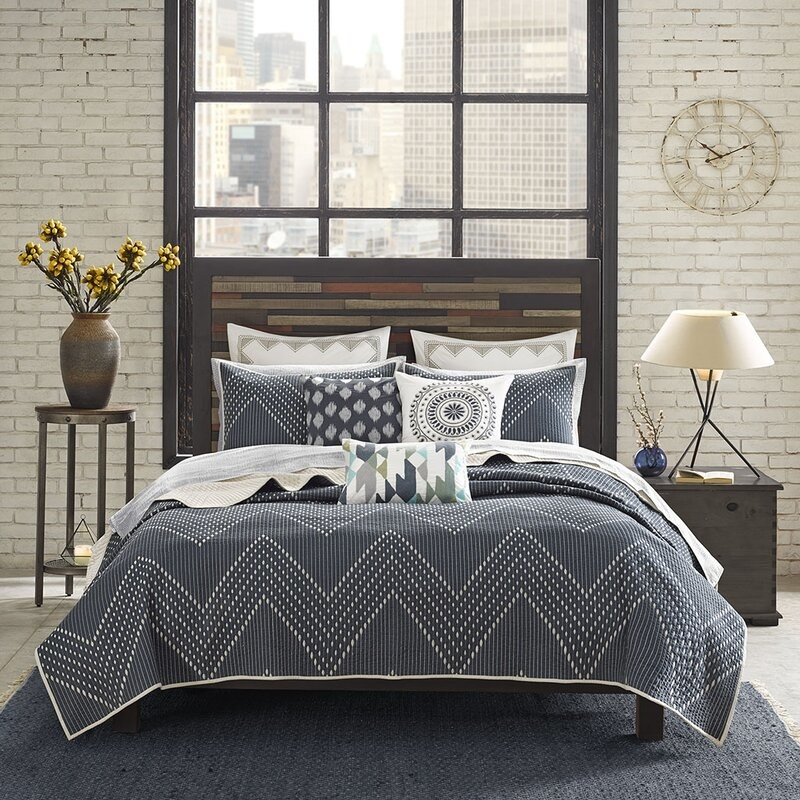 AllModern's Mercado coverlet set in a navy blue with a white chevron stitching
