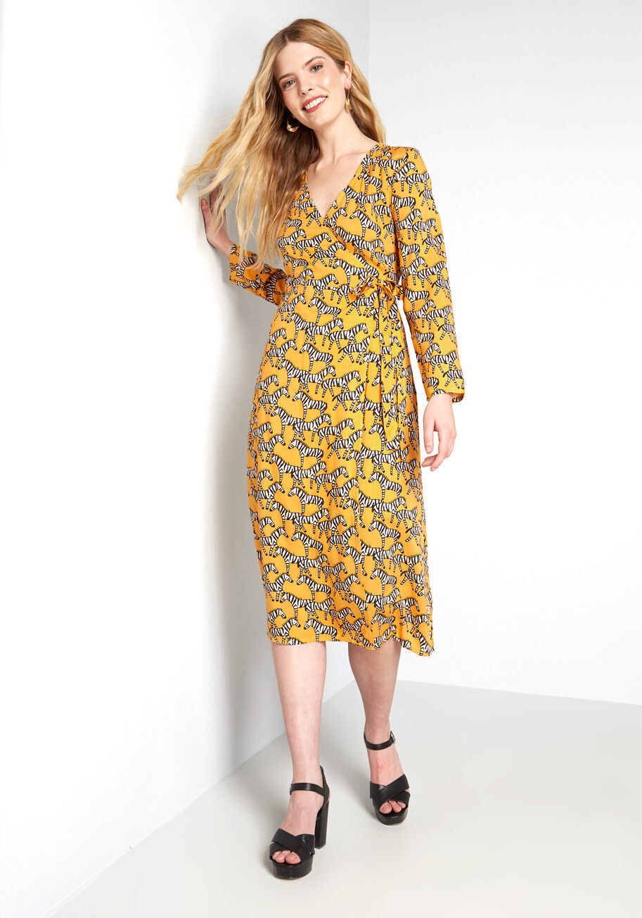 Yellow long-sleeved mid-length wrap dress with illustrations of zebras all over it