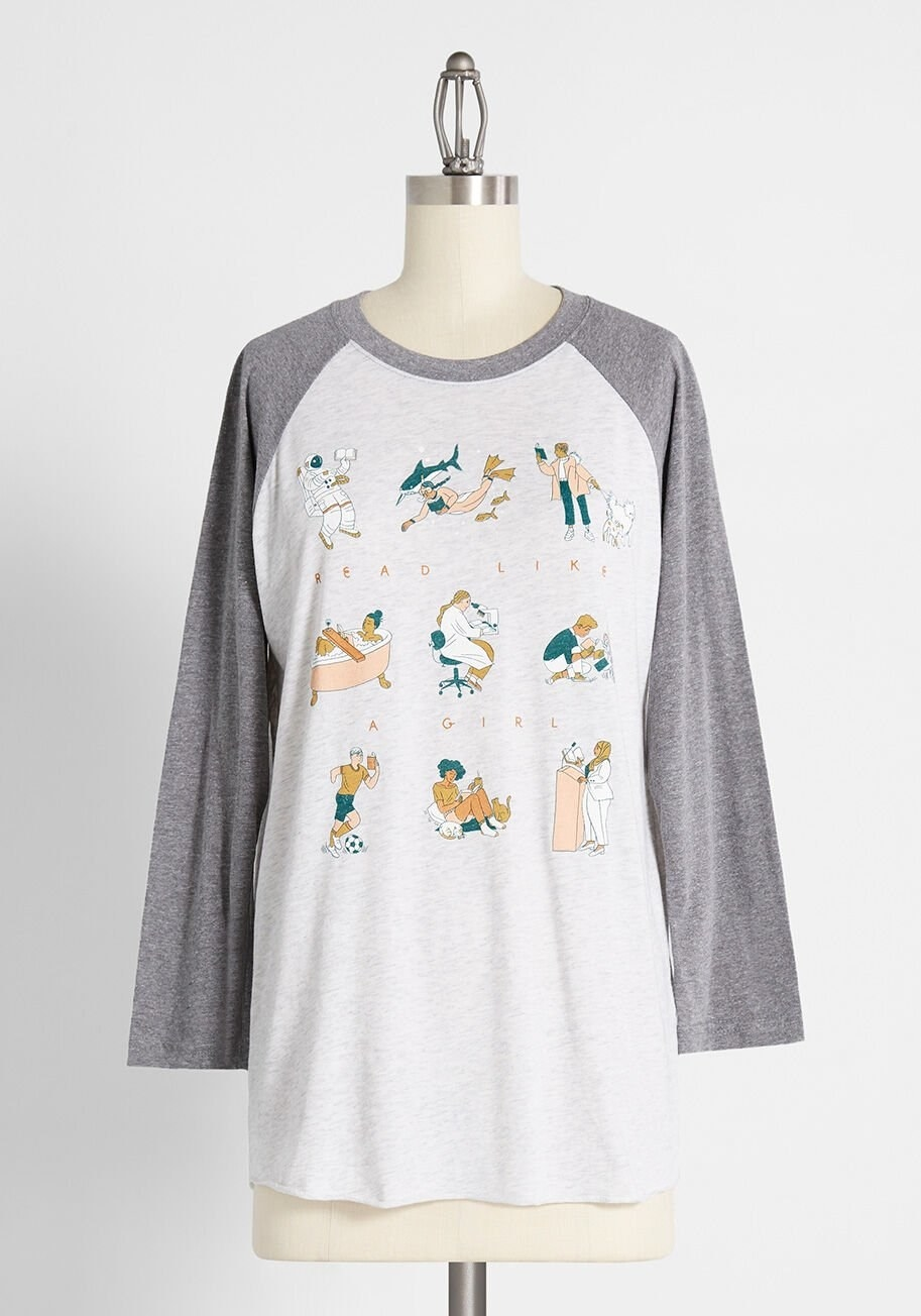 "The tee with grey arms and collar and white body with illustrations of girls reading in all different ways with the words ""Read like a girl"" through them"