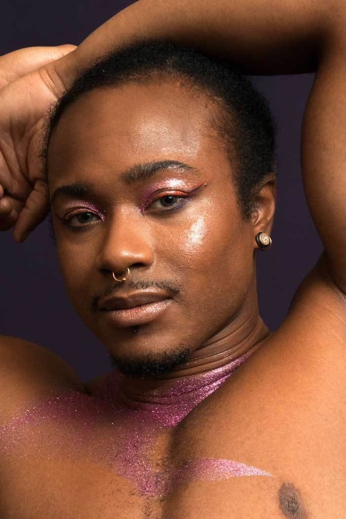 a model wearing the glitter on their eyes and chest