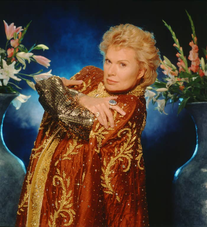 A publicity photo of Walter Mercado, where he is wearing a red cape with gold accents and has his arms crossed
