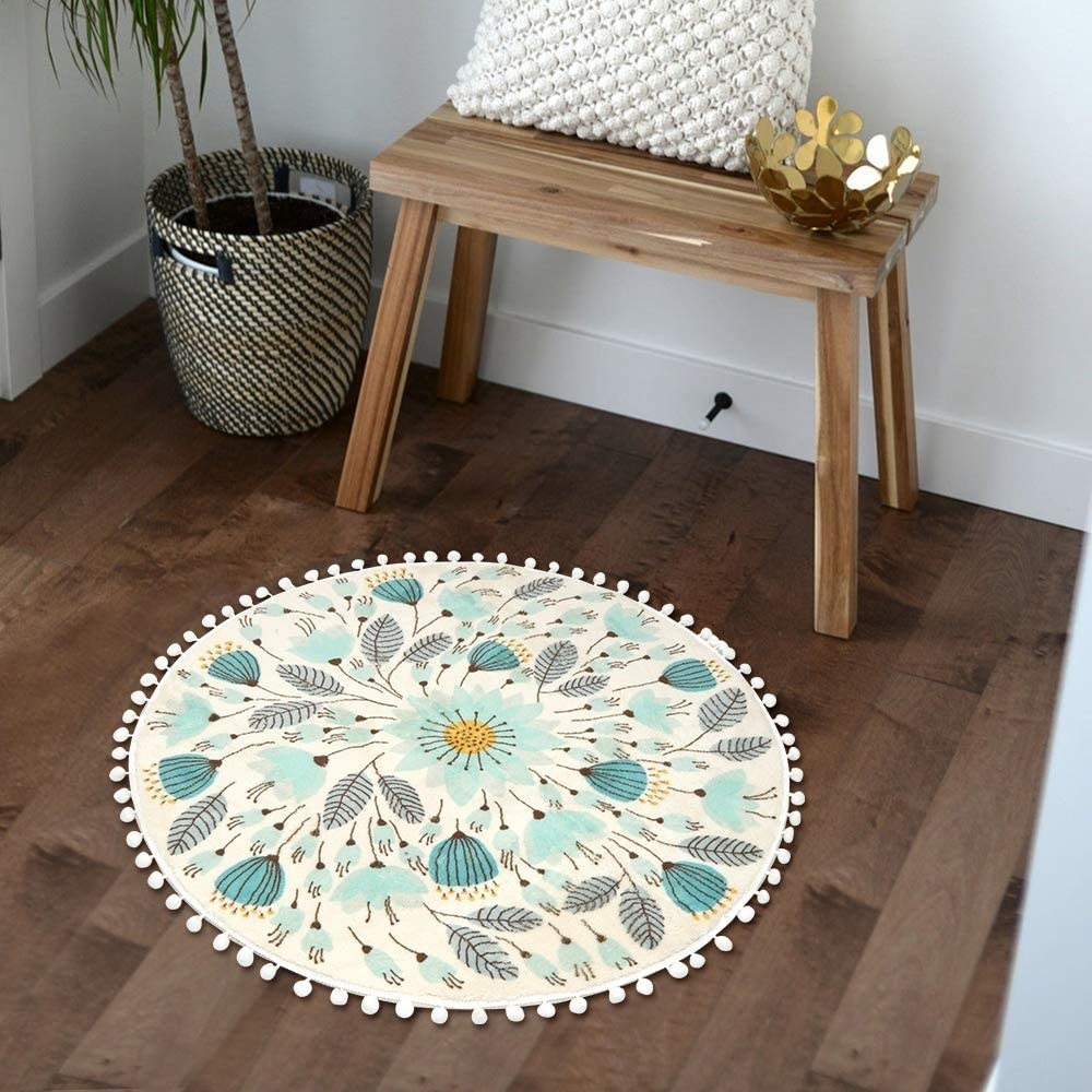 A cream, yellow, and blue floral rug with pom-poms around the circumference