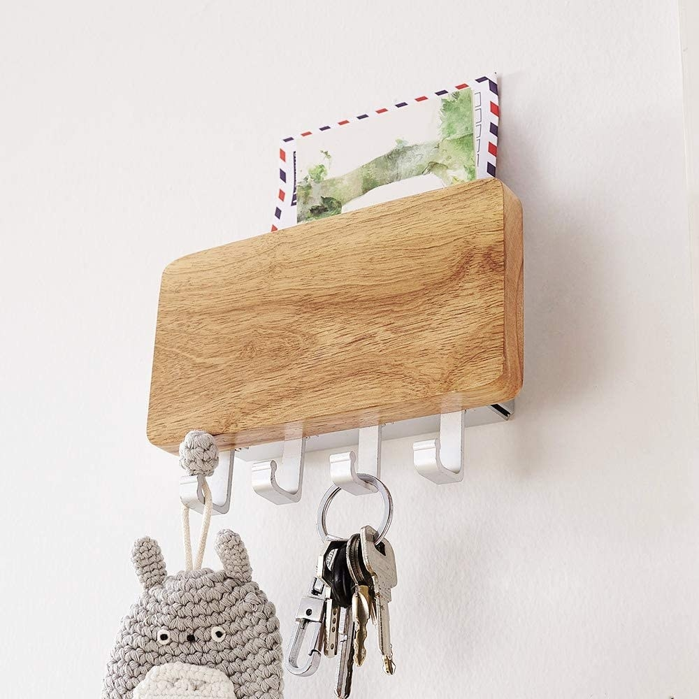The key holder mounted on a wall, containing one envelope, one set of keys, and a knitted key chain