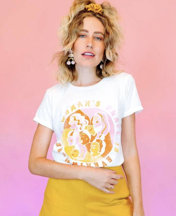 "White t-shirt with a pink, yellow, and orange illustration of women's faces in a circle with the words ""A woman's Place Is Everywhere"" written around it"
