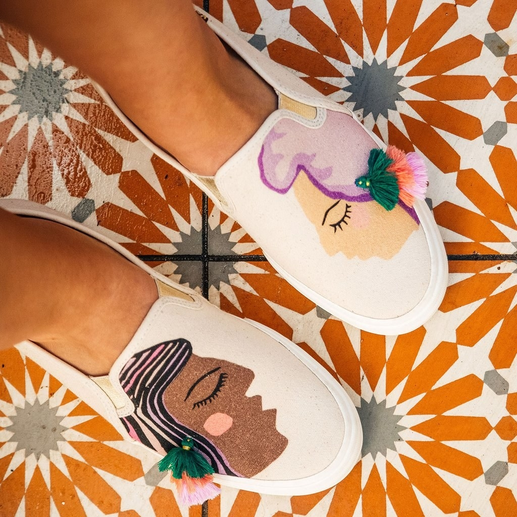 Person wearing the slip-on sneakers, which feature illustrations of two faces in different skin tones