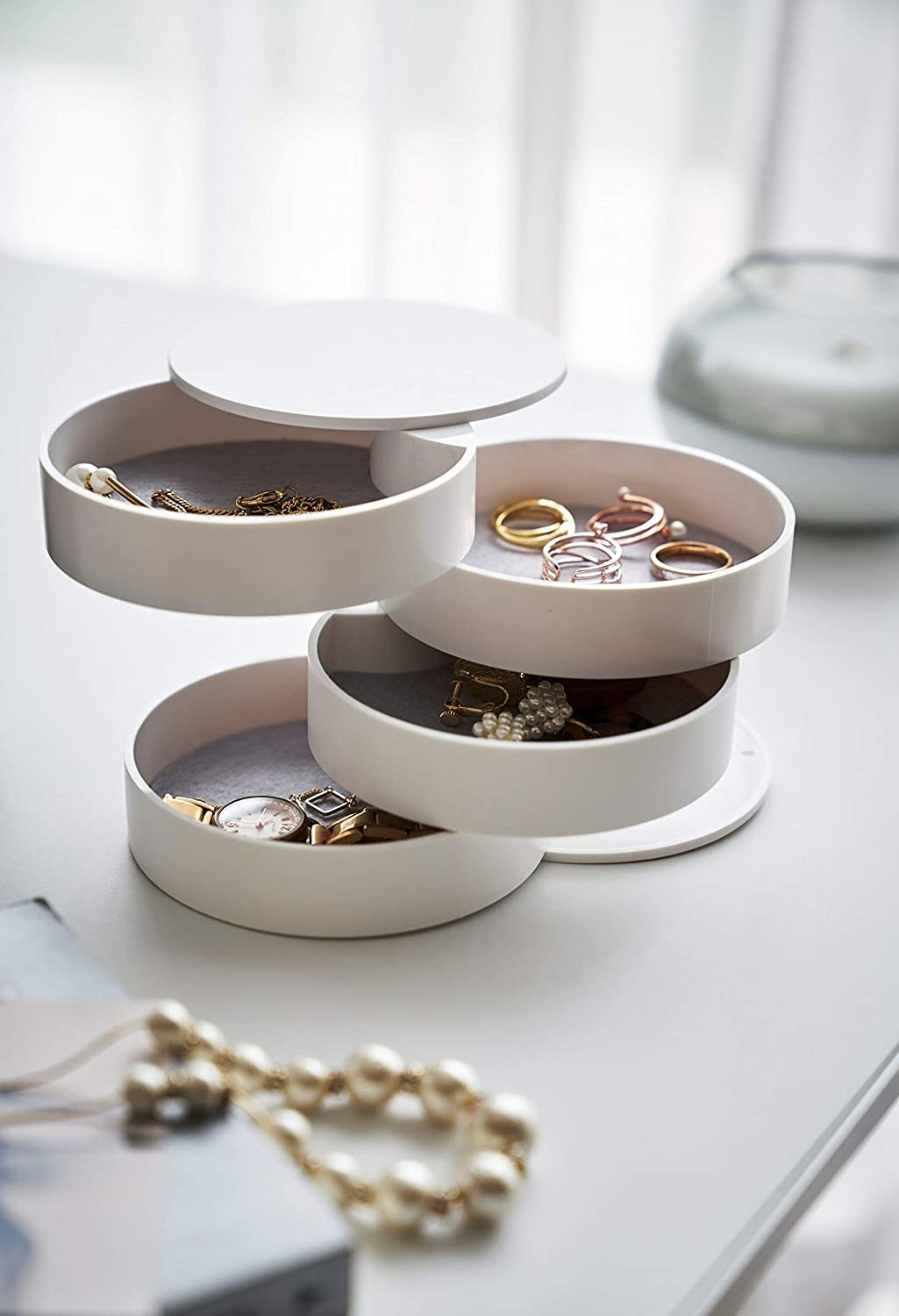 The circular jewelry box open showing the four containers that have jewelry in them