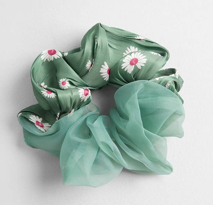 The scrunchie with half a satin-like fabric in sage with white and pink flowers on it and the other half a sheer sage fabric
