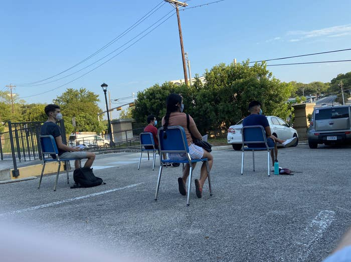 Four students in face masks sit in plastic chairs spaced 6 feet apart on an asphalt parking lot.