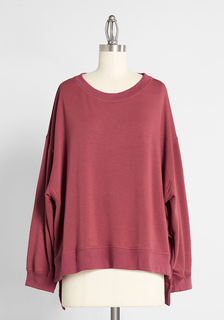 Red sweatshirt with dropped shoulders, side-slits, hi-lo hem, and a crew neck