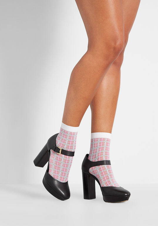 Model wearing the pink and white sheer plaid socks with a pair of chunky black heels